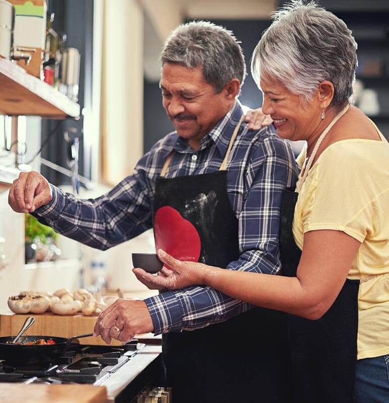 Older couple making food in a kitchen