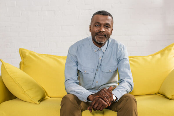 mature man sitting on yellow couch