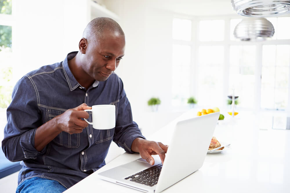 man looking at laptop while drinking coffee